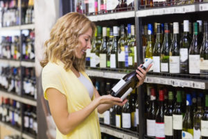 Smiling pretty blonde woman looking at a wine bottle in supermarket